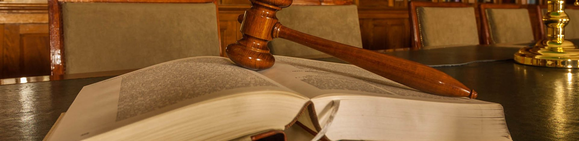 Photo of wooden judge's gavel in the library, focus on the gavel